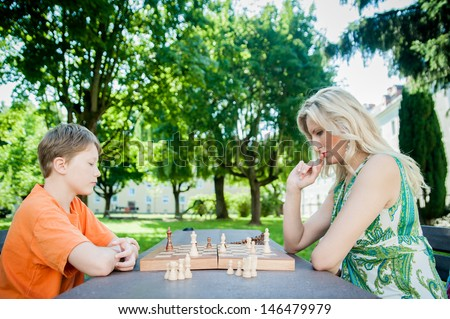 Mother and son playing chess in a park - stock photo