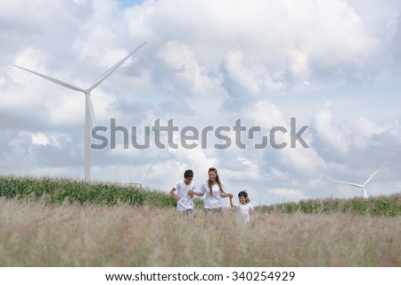 Mother and son playing in field with huge wind turbine in background
