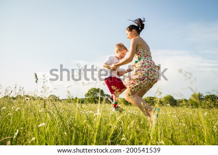 mother and son playing in the field - stock photo