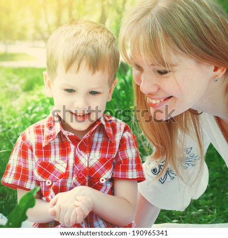 Mother and Son Playing in the Park, sitting on green grass, outdoor - stock photo