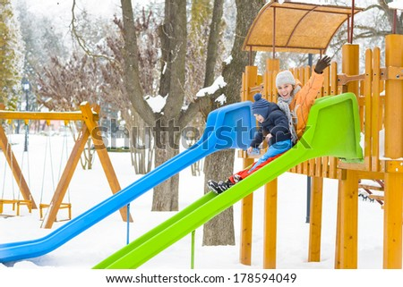 Mother and son playing on a slide in wintertime