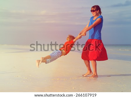 mother and son playing on summer tropical beach - stock photo