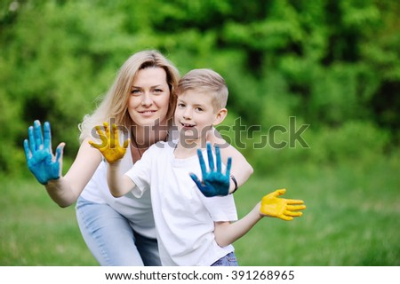 Mother and son playing on the background of green trees. Mom and son hands smeared with colored paint. - stock photo