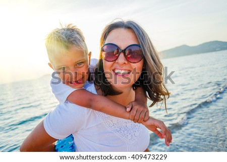 Mother and son playing on the beach against sunlight - stock photo