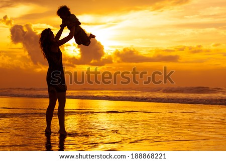 mother and  son playing on the beach in dawn time - stock photo