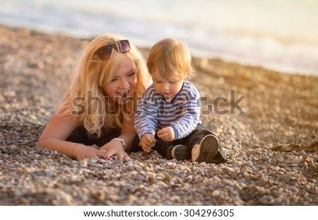 Mother and son playing on the beach. photographed at sunset - stock photo