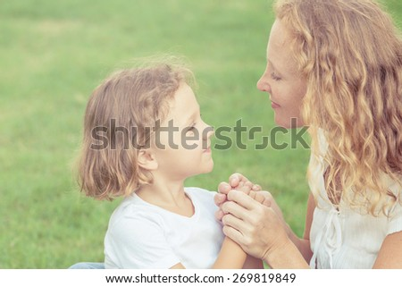 Mother and son playing on the grass at the day time. Concept of friendly family. - stock photo