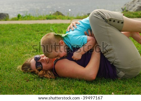 Mother and son playing outdoors on grass - stock photo
