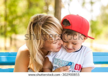 Mother and son playing together outdoors in park laughing fells fun and happy - stock photo