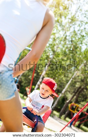 Mother and son playing together outdoors in park laughing ride on the swing - stock photo