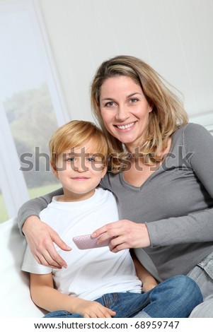Mother and son playing video game on telephone - stock photo