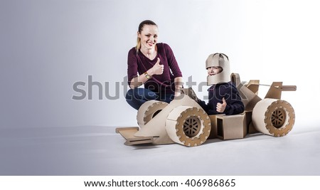 Mother and son playing with a large cardboard racing car.  thumbs up. happy family. - stock photo
