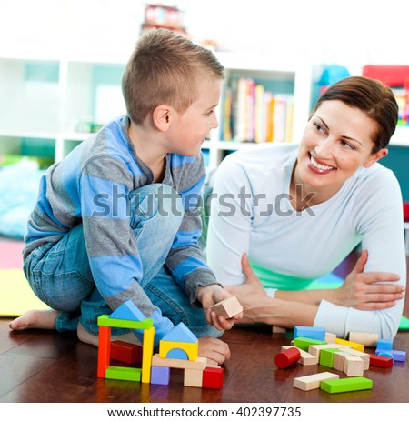 Mother and son playing with building blocks. - stock photo