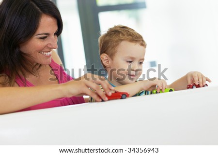 mother and son playing with toy cars on sofa. Copy space - stock photo
