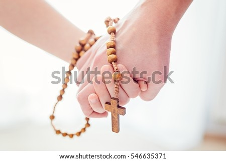 Mother and son praying together. Holding rosary in hand.