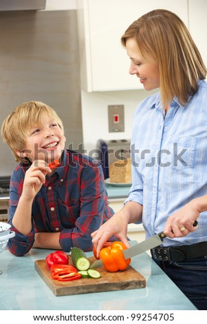 Mother and son preparing food in domestic kitchen - stock photo
