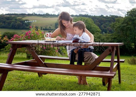 Mother and son, reading a book outdoor, summer day, eating sweet scones - stock photo