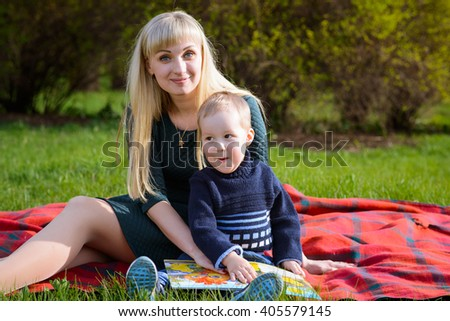 Mother and son reading a book sitting on a blanket on the lawn in the park in spring sunny day