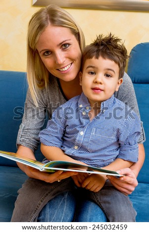 mother and son reading a book, symbol of maternal love, happiness, family, learning - stock photo