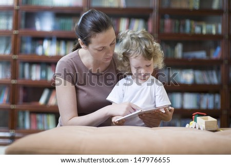 Mother and son reading book at home - stock photo