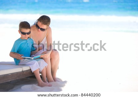 Mother and son reading book at tropical beach - stock photo