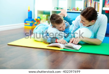 Mother and son reading together - stock photo