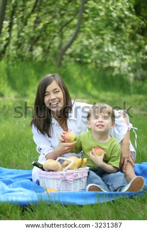 mother and son relaxing - family picnic in the forest