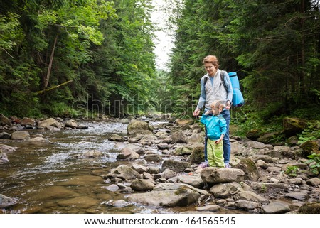 Mother and son resting by a stream in mountains. The boy throwing stones in water.
