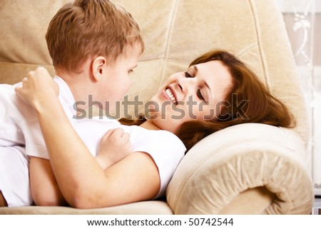 mother and son resting on sofa indoor - stock photo