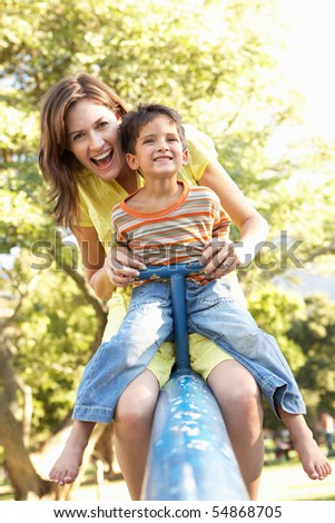 Mother And Son Riding On See Saw In Playground - stock photo