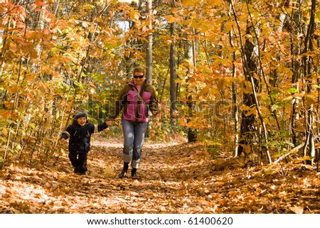 Mother and son running in autumn forest - stock photo