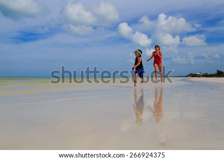 mother and son running in water on tropical beach