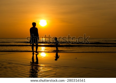 Mother and son silhouettes on beach at sunset