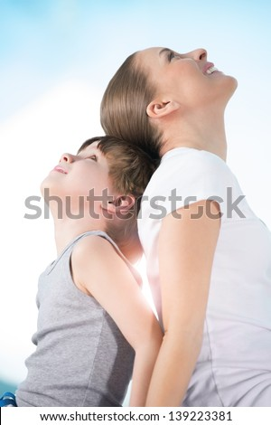 Mother and son sitting back to back together and looking upwards while dreaming enjoying moments of happiness together - stock photo