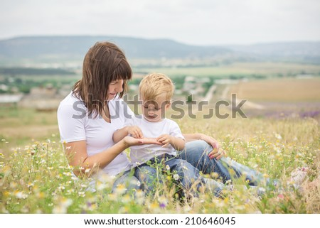 mother and son sitting in a field