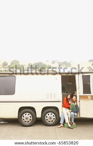 Mother and son sitting in doorway to recreational vehicle - stock photo