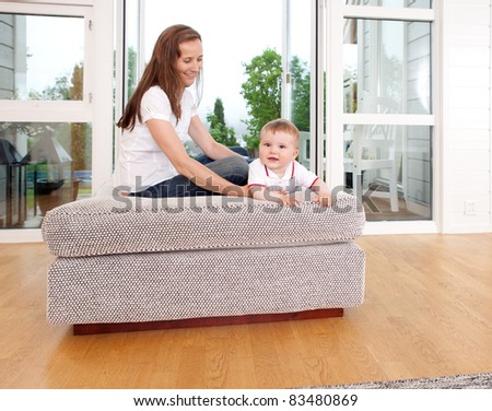 Mother and son sitting in the living room playing - stock photo