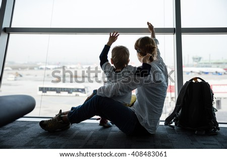 Mother and son sitting near window in airport and waving hands to airplanes