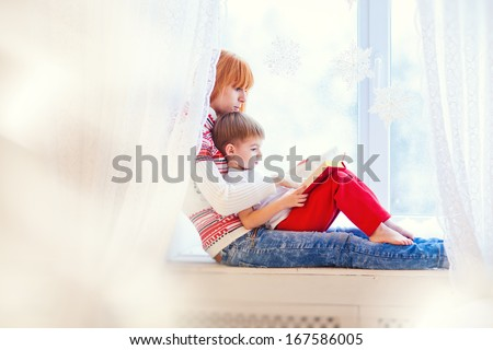 Mother and son sitting on a windowsill and read a book. - stock photo