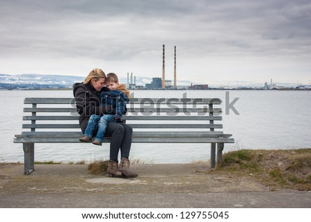 Mother and son sitting on bench with industrial backdrop - stock photo
