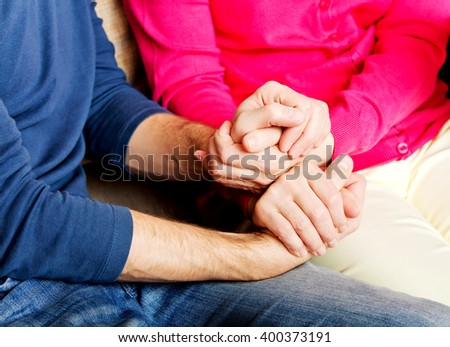 Mother and son sitting on couch and holding hands  - stock photo