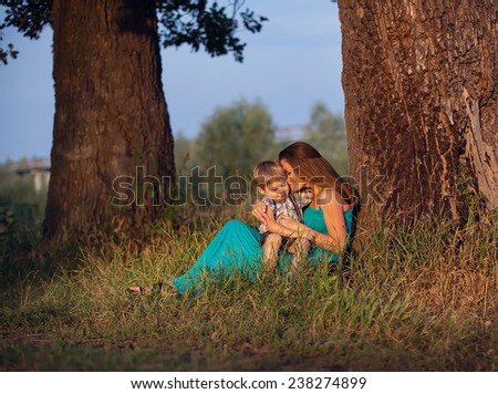 mother and son sitting under a the big tree - stock photo
