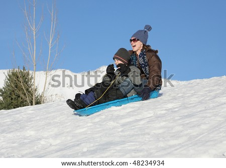 mother and son sledding down a snowy hill on a blue sled - stock photo