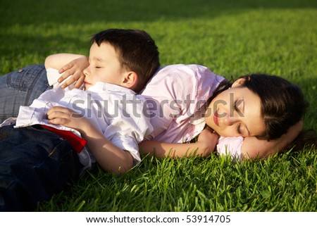 mother and son sleeping on grass - stock photo