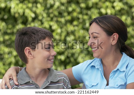 Mother and son smiling at each other - stock photo