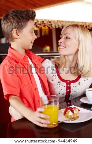 Mother and son spending time together at a cosy cafe - stock photo