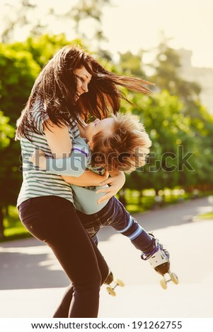 Mother and son spinning in summer park - stock photo