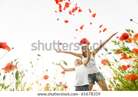 mother and son stand in poppy field - stock photo