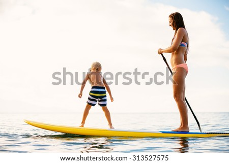 Mother and Son Stand Up Paddling Together Having Fun in the Ocean - stock photo