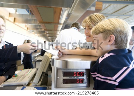 Mother and son (8-10) standing at check-in desk in airport, woman receiving boarding passes from female check-in attendant, smiling, side view - stock photo